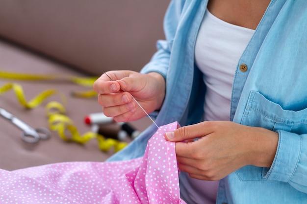 Processus de couture. femme au foyer coud à la maison à l'aide de divers accessoires et fournitures de couture