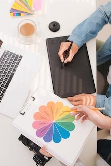 Processus de coworking, équipe de concepteurs travaillant sur ordinateur dans un bureau moderne.