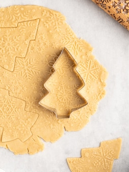 Processus de cuisson du dessert traditionnel de noël et du nouvel an, biscuits au pain d'épice, rouleau à pâtisserie avec motif de flocons de neige dessus, étoiles d'anis et cannelle, noël et hiver, disposition du cadre