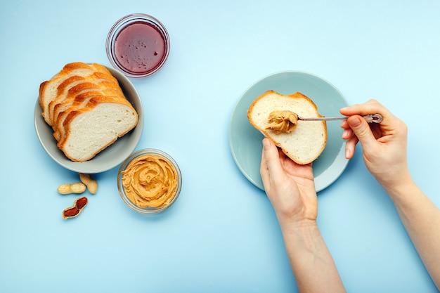 Processus de cuisson du petit-déjeuner, étalement du pain grillé avec de la pâte de beurre d'arachide sur la table de couleur bleue