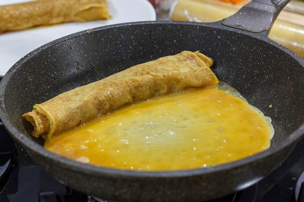 Le processus de cuisson du rouleau d'omelette japonaise. faire frire une omelette dans une poêle