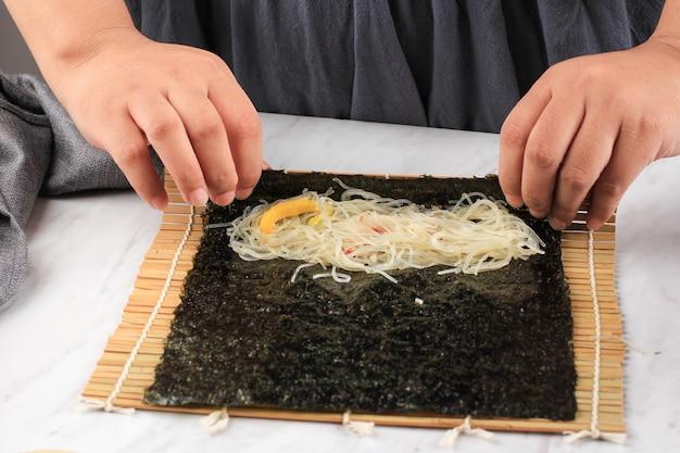 Processus de cuisson: faire du kimmari ou du gimmari, du laver de nori roulé avec des vermicelles sautés ou des nouilles en verre, un rouleau à la main de chef nori