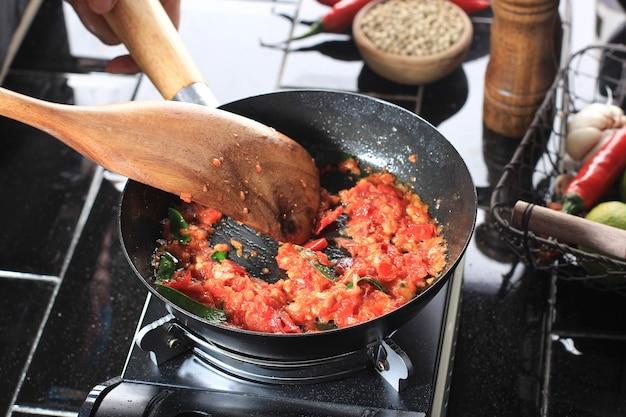 Processus de cuisson faire sauter sambal ou sambel ou sauce épicée avec des feuilles de citron vert sur une casserole dans la cuisine