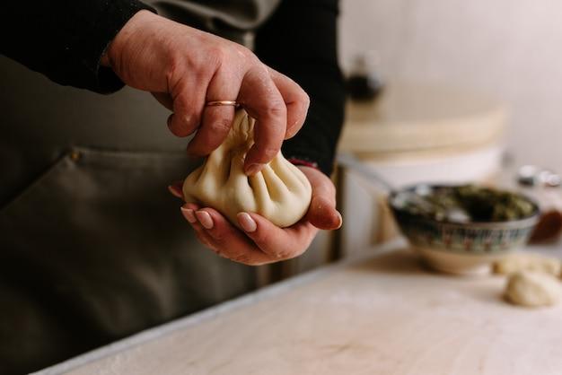 Processus de cuisson. femme faisant du khinkali pour son gros plan familial. préparer un repas traditionnel géorgien de pâte et de viande à la cuisine. cuisine nationale, concept de processus de cuisson