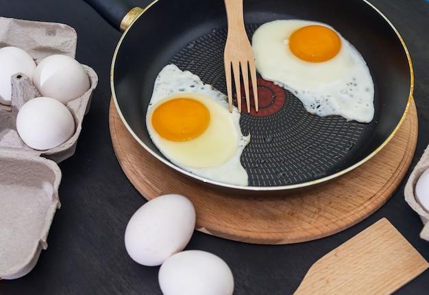 Processus de cuisson des œufs frits. deux œufs au plat dans une casserole et des œufs crus sur un bois sombre.