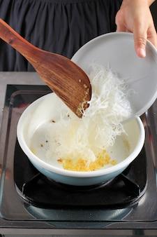 Processus de cuisson: verser des nouilles de verre ou des vermicelles dans la casserole, étape par étape, faire du japchae ou des nouilles de cellophane sautées.