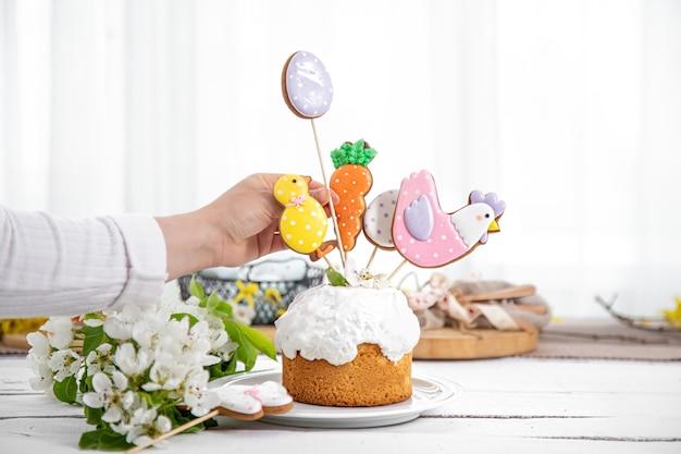 Le processus de décoration d'un gâteau de fête avec du pain d'épice et des fleurs. le concept de la préparation des vacances de pâques.