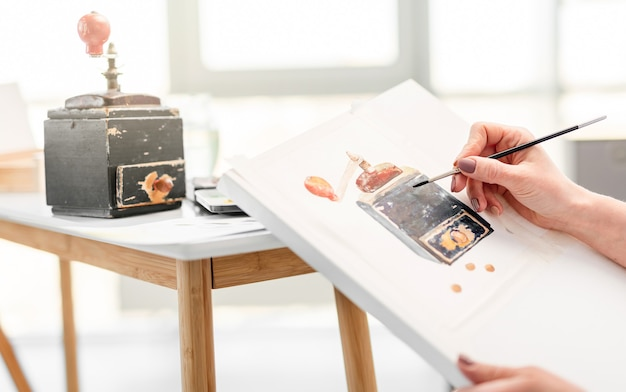 Processus de dessin de la nature, la main de l'artiste avec un pinceau dessine une boîte à musique noire à l'aquarelle