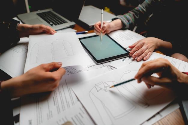 Le processus du groupe de personnes conçoit de nouveaux vêtements sur le papier