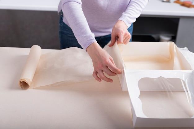 Processus d'emballage cadeau dans une boîte en carton blanc. confiseur emballe des bonbons.