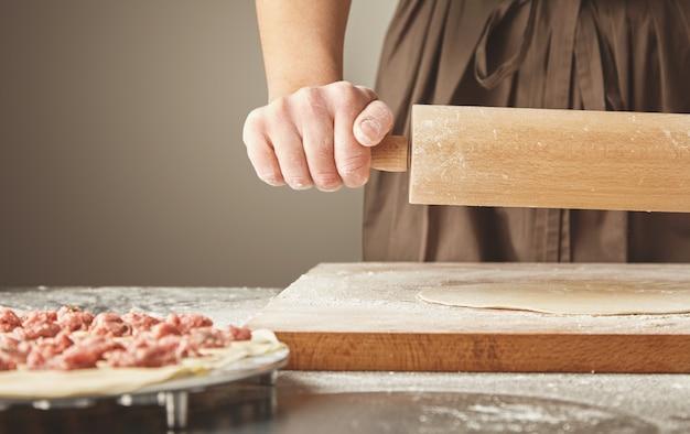 Processus étape par étape de fabrication de boulettes, de raviolis ou de pelmeni faits maison avec une garniture de viande hachée à l'aide d'un moule à ravioli ou d'une machine à ravioli isolé sur le côté droit. aplatir la pâte avec un rouleau à pâtisserie