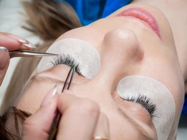 Processus d'extension des cils dans un salon de beauté. créez du volume dans les cils.