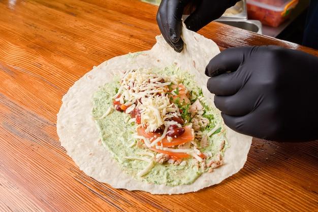 Processus de fabrication de burrito. le chef enveloppe des pita farcis sur une table en bois. plat mexicain.