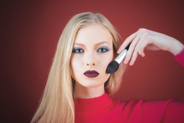 Processus de fabrication du maquillage. portrait de jeune femme blonde. appliquer le ton sur la peau. cosmétique. base pour un maquillage parfait. fards à paupières. pinceau de maquillage.
