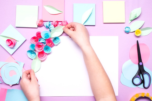 Le processus de fabrication de fleurs en papier à partir d'autocollants de cartes postales colorées. petite fille faisant des fleurs en papier