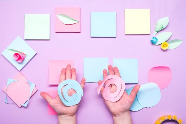 Le processus de fabrication de fleurs en papier à partir d'autocollants de cartes postales colorées. petite fille prépare une carte pour la fête des mères.