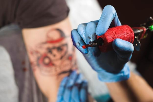 Processus de fabrication de gros plan de tatouage, homme créant une image à portée de main avec elle dans le salon