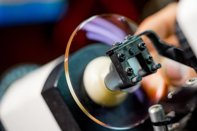 Processus de fabrication de lunettes. soins de santé. homme polissant des verres dans un magasin d'optique. broyer la lentille dans la lunette.