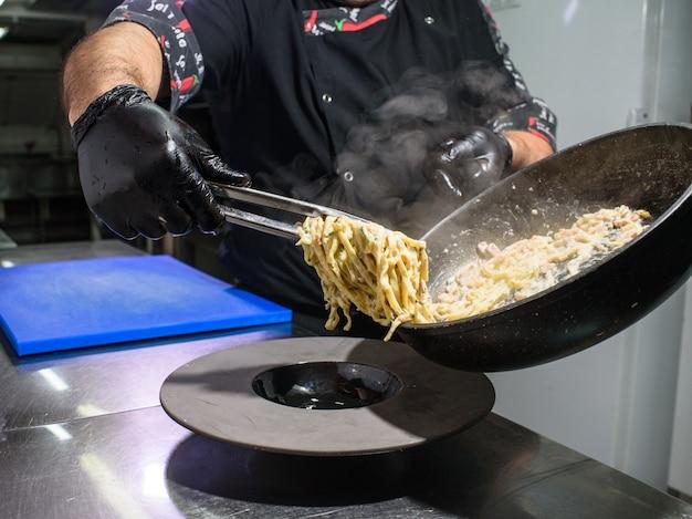 Le processus de fabrication de pâtes carbonara pour les clients du restaurant. nourriture savoureuse.