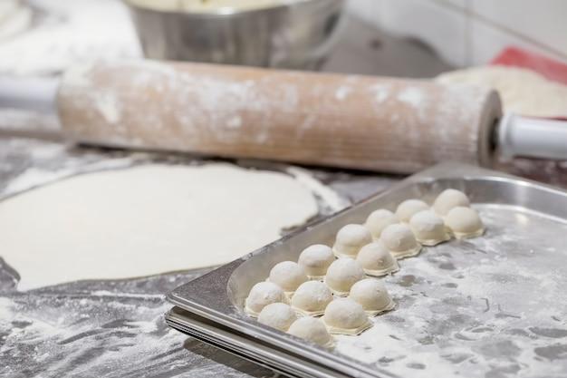 Processus de fabrication de pelmeni, de raviolis ou de boulettes de viande russes. pelmeni non cuit maison