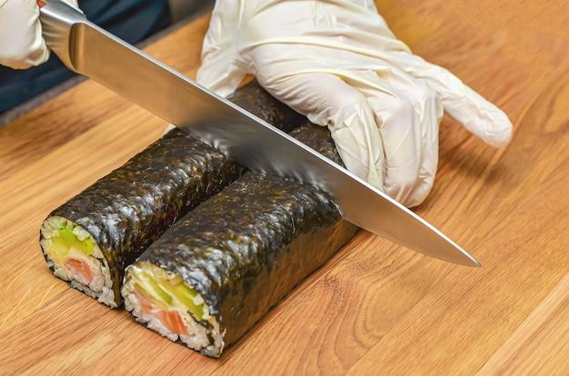Le processus de fabrication des sushis japonais. un couteau à la main coupe un gros plan de rouleau sur une planche de bois. mains femelles dans des gants en caoutchouc