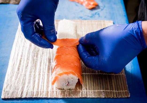 Processus de fabrication de sushis et de rouleaux dans la cuisine du restaurant. chefs mains avec couteau.