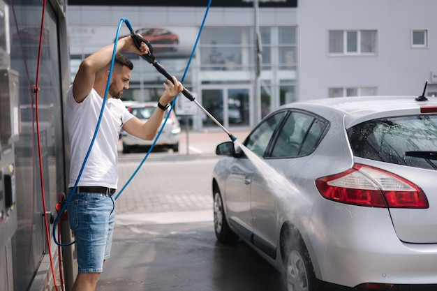 Processus de l'homme lavant sa voiture dans une station de lavage de voiture en libre-service