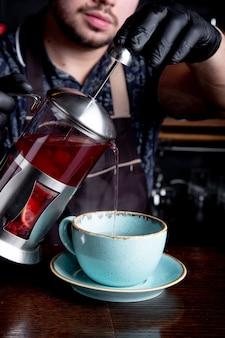 Processus d'infusion de thé, cérémonie du thé. le barman verse du thé chaud aux fruits ou aux baies dans la tasse.