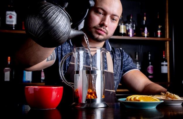 Processus d'infusion de thé, cérémonie du thé. le barman verse de l'eau chaude dans la bouilloire pour préparer le thé aux fruits de mer