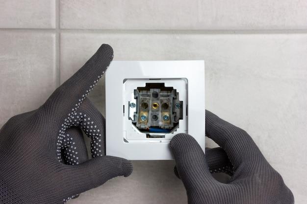 Le processus d'installation d'une prise électrique mains masculines dans des gants gris a mis une rosette blanche
