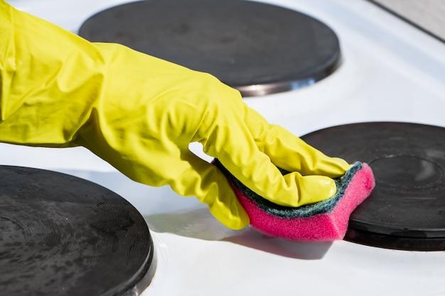 Le processus de lavage d'une cuisinière électrique. une main dans un gant jaune nettoie la surface blanche de la saleté.