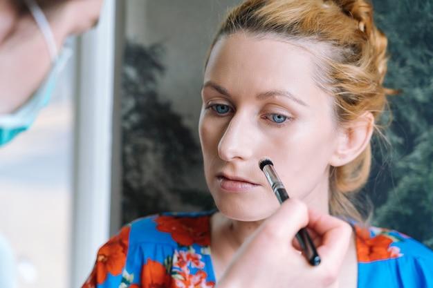 Processus de maquillage. maquilleuse appliquée au pinceau sur le visage du modèle. portrait de jeune femme au gingembre dans un salon de beauté. main de maquilleuse avec pinceau pour une peau parfaite et une couleur de fard à paupières