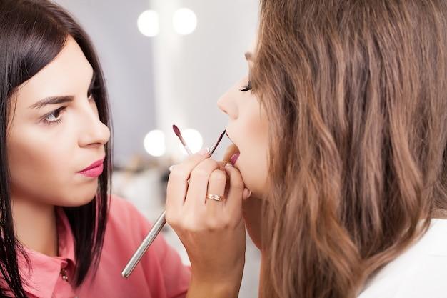 Processus de maquillage professionnel. artiste fait le style de visage