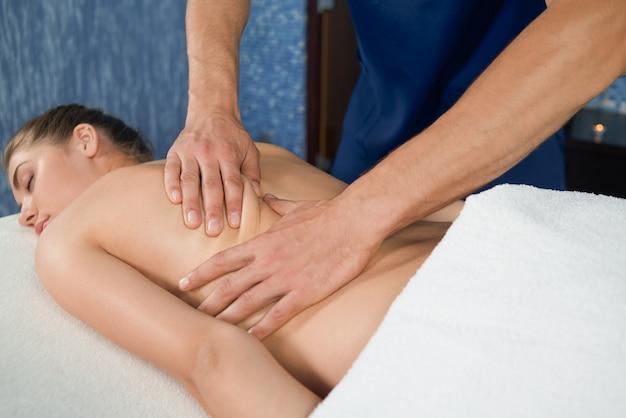 Processus de massage du dos à une cliente détendue