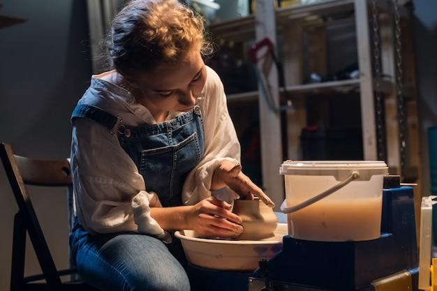 Le processus de modelage d'un vase en argile montre un jeune potier dans son atelier.