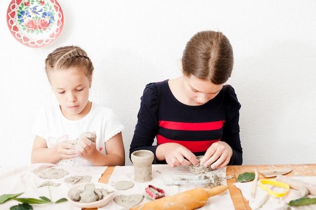 Processus de modélisation des figures d'argile blanche, les filles font des arts à la leçon