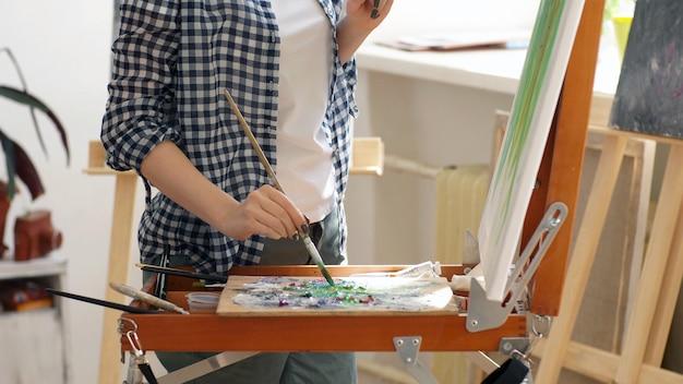 Processus de peinture en gros plan dans l'atelier, l'artiste dessine une peinture à l'huile à l'aide d'une palette