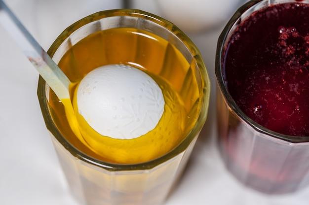 Le processus de peinture des oeufs de pâques avec un colorant alimentaire et de la cire fondue.