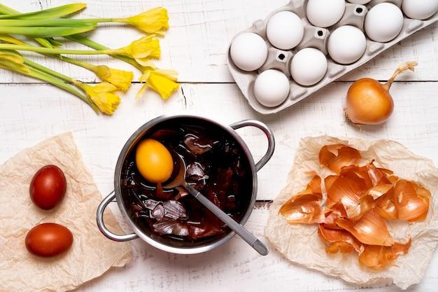 Le processus de peinture des œufs de pâques avec des colorants végétaux naturels, des cosses d'oignon, sur une table en bois blanc, une vue de dessus des œufs de poule et des jonquilles jaunes.
