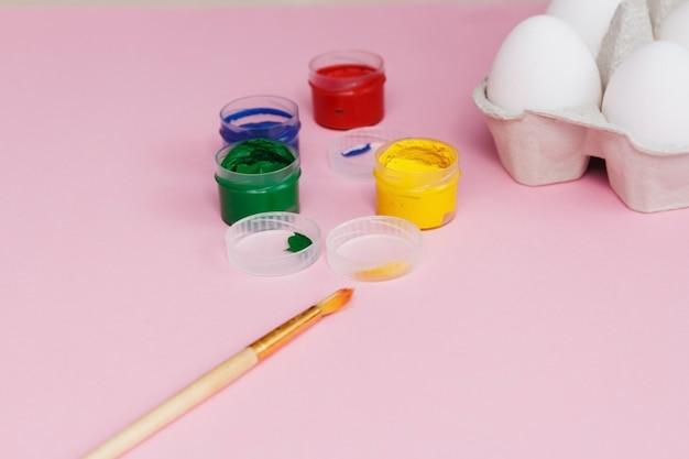 Processus de peinture des œufs pour pâques, boîte à œufs, œufs de pâques, pinceaux et peintures sur rose