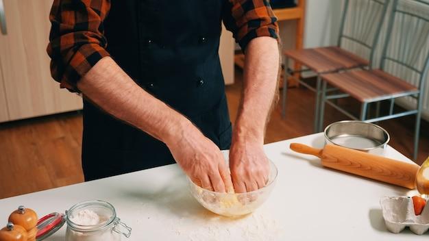 Processus de préparation de la pâte à pâtisserie faite par l'homme boulanger. chef âgé à la retraite avec saupoudrage uniforme, tamisage, tamisage des ingrédients bruts à la main et mélange avec de la farine pour cuire des pizzas maison, du pain.