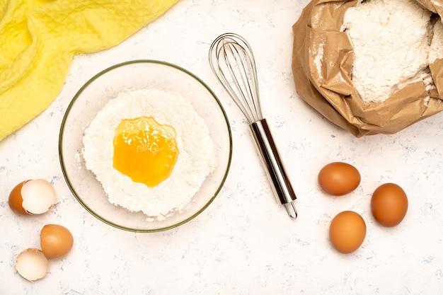 Le processus de préparation de la pâte pour crêpes avec des ingrédients sur une table lumineuse, les œufs et la farine sont fouettés avec un mélangeur.