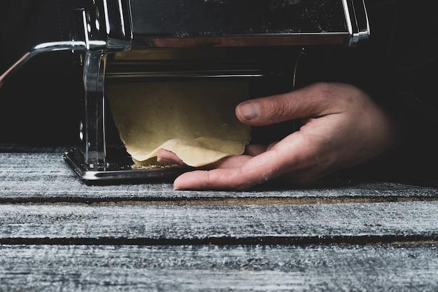 Le processus de préparation des pâtes fraîches. chef préparant la pâte de pâtes sur une machine à écrire, espace de copie