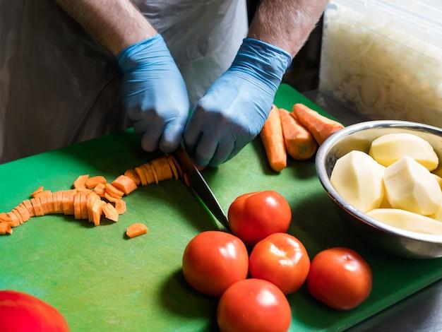 Processus de préparation des repas. chef coupant la carotte. recette de plat de légumes sains