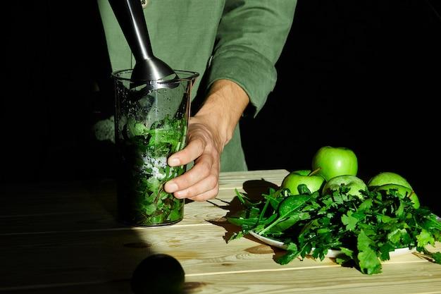 Processus de préparation de smoothie de désintoxication vert avec un mélangeur, jeune homme mains cuisson smoothie sain.