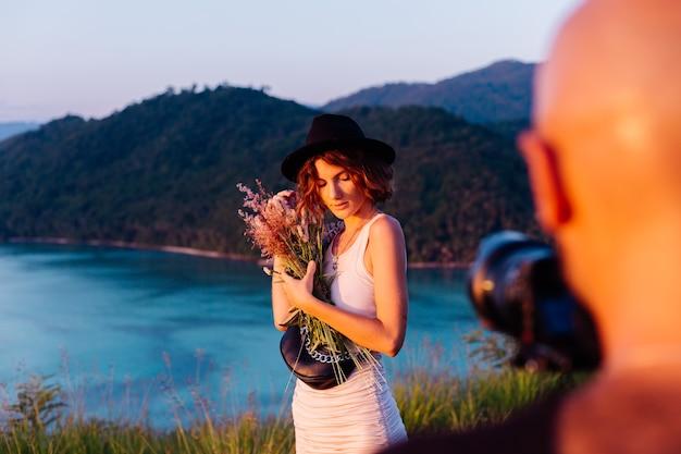 Processus de prise de vue vidéo l'homme prend une vidéo sur l'appareil photo professionnel de la jeune femme élégante blogueuse en vacances vue tropicale