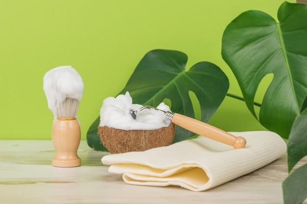 Le processus de rasage avec des outils vintage sur fond de feuilles vertes.