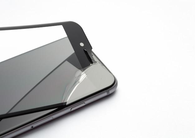 Processus de remplacement du verre de protection sur smartphone sur fond blanc.