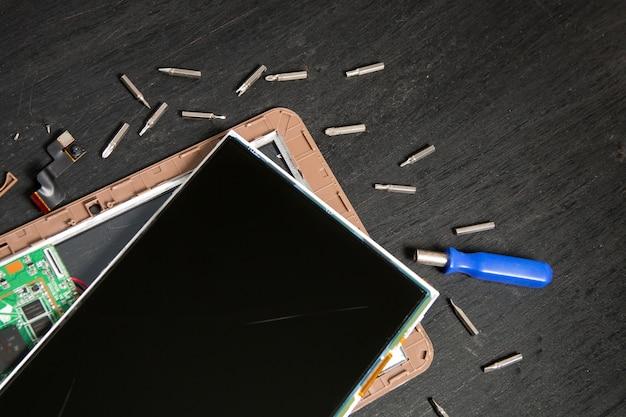 Processus de réparation de tablette pc près du tournevis et du foret sur une surface en bois noire démontée