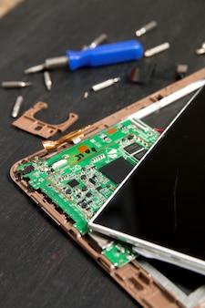 Processus de réparation de tablette pc près de tournevis et peu sur un fond en bois noir.